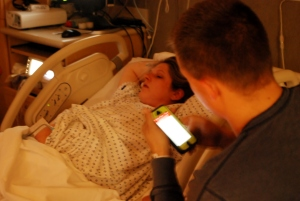 Having a little down time during labor, daddy (Art) updates facebook while mama (Neva) rests